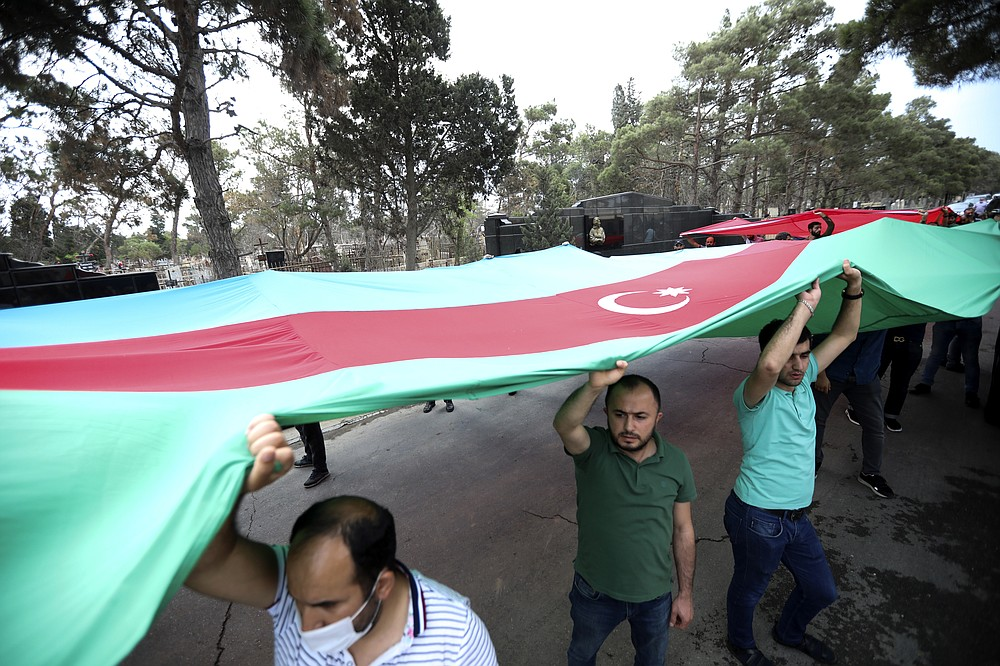 People carry an Azerbaijan's national flag during a funeral ceremony of Maj. Gen. Polad Hashimov who was killed in fighting Tuesday along with five other servicemen at a cemetery in Baku, Azerbaijan, Wednesday, July 15, 2020. Skirmishes on the volatile Armenia-Azerbaijan border escalated Tuesday, marking the most serious outbreak of hostilities between the neighbors since the fighting in 2016. (AP Photo/Aziz Karimov)