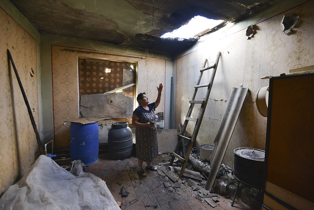 A local woman shows damage in her house after the shelling by the Azerbaijan side in the Aygepar village in Armenia's Tavush region, Armenia, Wednesday, July 15, 2020. Three days of fighting between Armenian and Azerbaijani forces have killed at least 16 people in the worst outbreak of hostilities between the neighboring countries in years. (Karo Sahakyan/PAN Photo via AP)