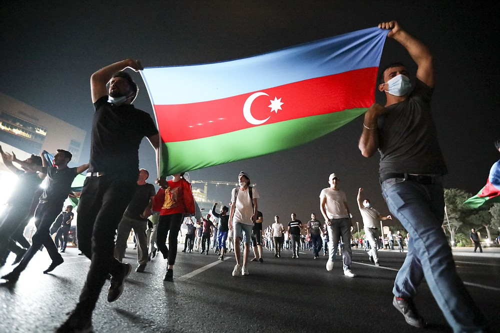 People carry an Azerbaijn's national flag as they rally in support of Azerbeijan's Army in Baku, Azerbaijan, Tuesday, July 14, 2020. Skirmishes on the volatile Armenia-Azerbaijan border escalated Tuesday, marking the most serious outbreak of hostilities between the neighbors since the fighting in 2016. (AP Photo/Aziz Karimov)