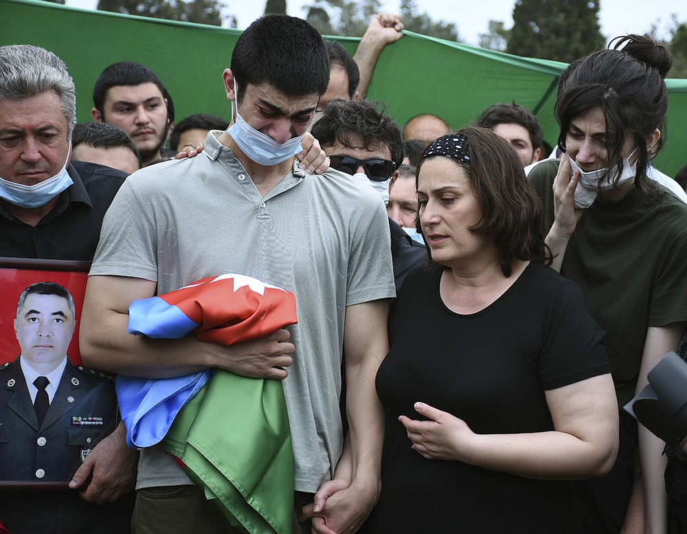 Elvin, son of Col. Ilgar Mirzayev, who was killed in fighting Tuesday along with five other servicemen holds an Azerbaijan's national flag standing with his mother and widow of Ilgar Mirzayev during the funeral ceremony in Baku, Azerbaijan, Wednesday, July 15, 2020. Skirmishing on the volatile Armenia-Azerbaijan border escalated Tuesday, marking the most serious outbreak of hostilities between the neighbors since the fighting in 2016. (AP Photo)