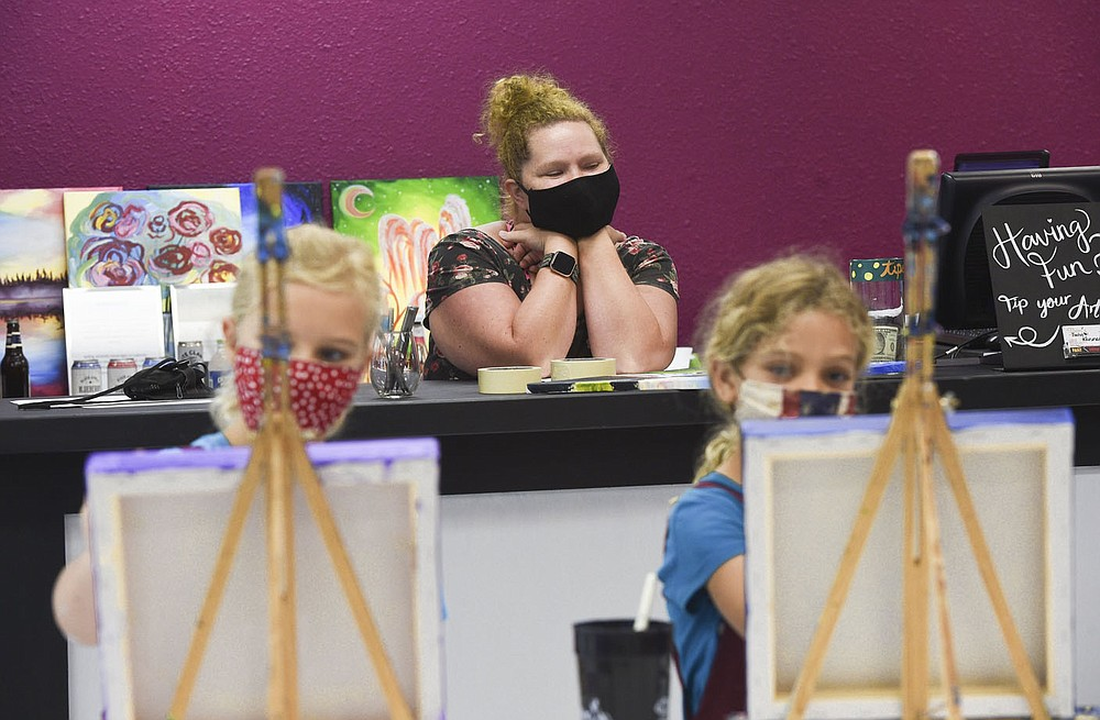 """Lead artist and manager Shelby Nichols (center) looks on as Teryn and Cecilia Kaiser of Bentonville (from foreground left) paint, Thursday, July 16, 2020 during a carnival themed kids painting camp in Bentonville. """"This is the most fun I've ever had at a job so it's really important to keep our business healthy right now and protect our customers,"""" Shelby Nichols, lead artist and manager, said of their mask policy. """"For a lot of people painting is their safe space."""" People not comfortable with in-person classes can also pick up an art kit with brushes, a canvas and instructions she added. Check out nwaonline.com/200717Daily/ for today's photo gallery.  (NWA Democrat-Gazette/Charlie Kaijo)"""