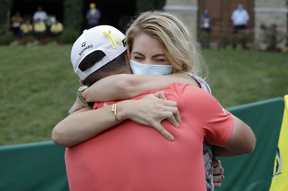 Jon Rahm, of Spain, left, celebrates with his wife, Kelley Cahill, after winning the Memorial golf tournament, Sunday, July 19, 2020, in Dublin, Ohio. (AP Photo/Darron Cummings)