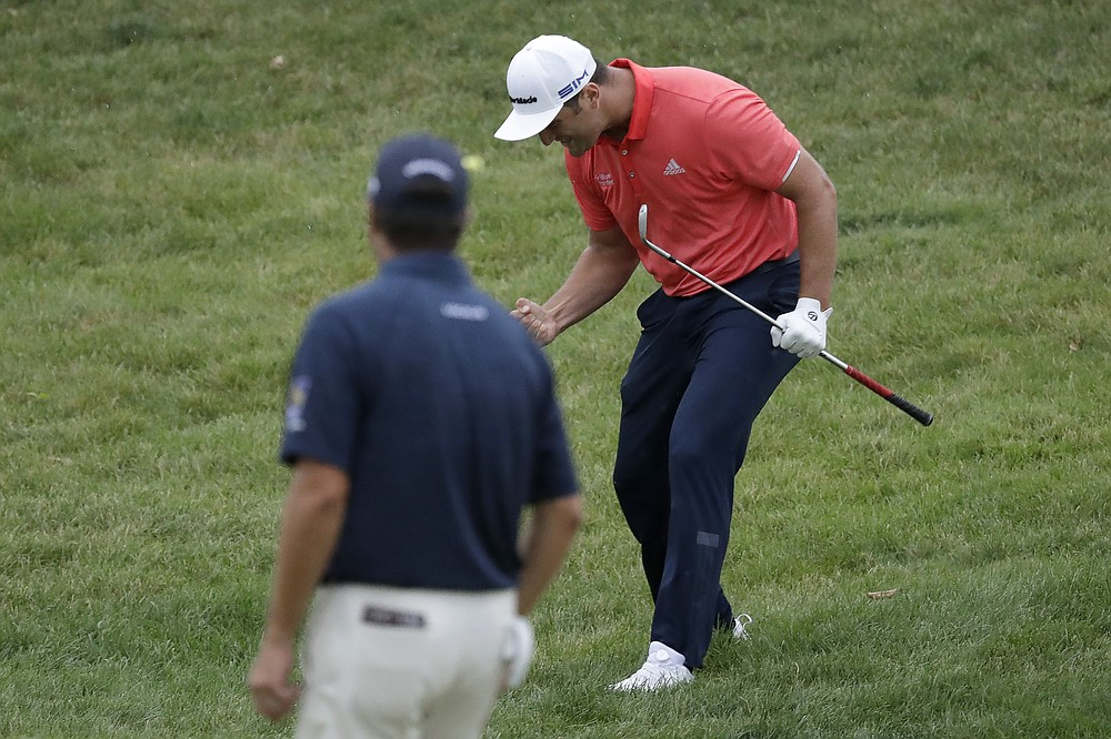 Jon Rahm, of Spain, right, celebrates after chipping for birdie on the 16th hole as Ryan Palmer watches during the final round of the Memorial golf tournament, Sunday, July 19, 2020, in Dublin, Ohio. (AP Photo/Darron Cummings)