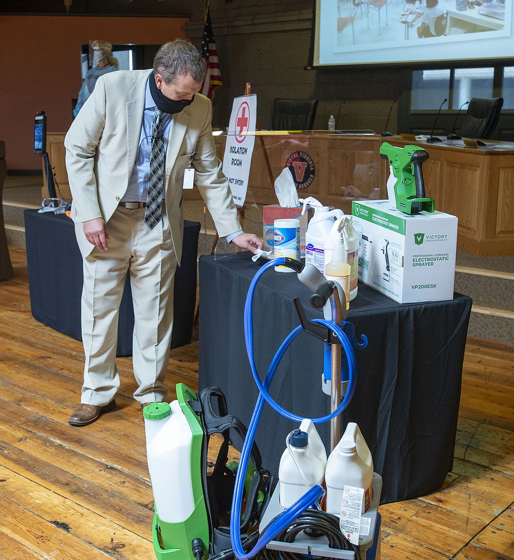 Bristol, Va., Public Schools Superintendent Dr. Keith Perrigan shows some of the items that will be used to clean the school throughout the year Thursday, July 16, 2020, in Bristol, Va. (David Crigger/Bristol Herald Courier via AP)