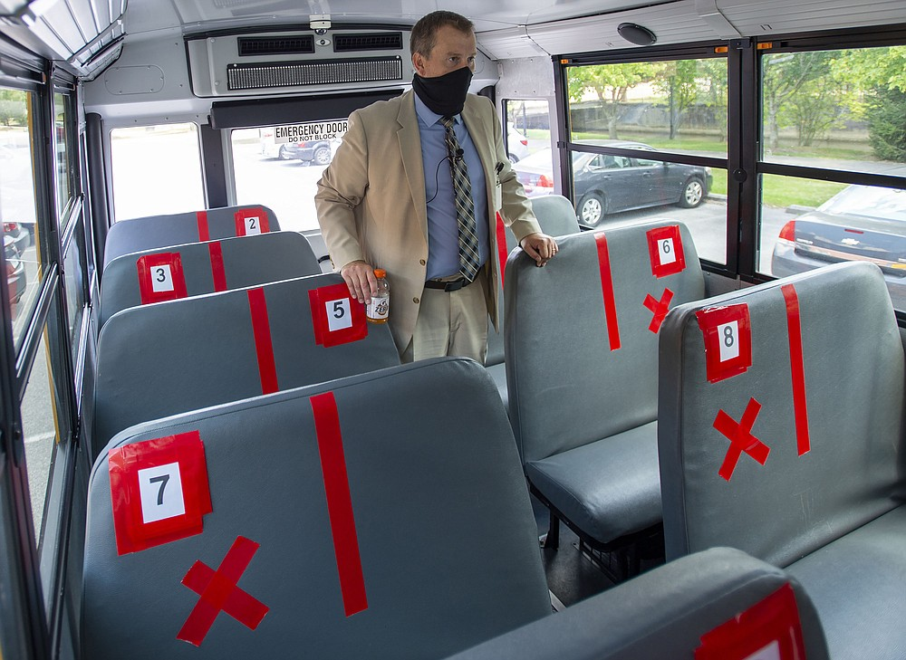 Superintendent Dr. Keith Perrigan shows the new seating configuration on the school buses for the upcoming school year, Thursday, July 16, 2020, in Bristol, Va. A maximun of 22 students can be on the bus. (David Crigger/Bristol Herald Courier via AP)