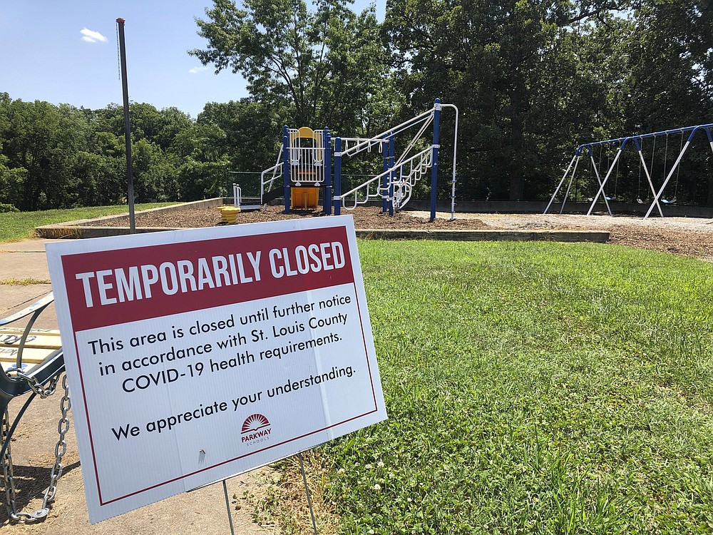 A sign alongside a playground at Hanna Woods Elementary School in the Parkway School District in suburban St. Louis indicates that the playground is closed due to the coronavirus pandemic, Saturday, July 18, 2020. Parkway has formulated a flexible plan to reopen schools when the fall semester begins Aug. 24. Just how bad the virus is at the time will determine if schools open completely, if they mix online and in-person classes, or if they are forced to go strictly virtual. (AP Photo/Jim Salter)