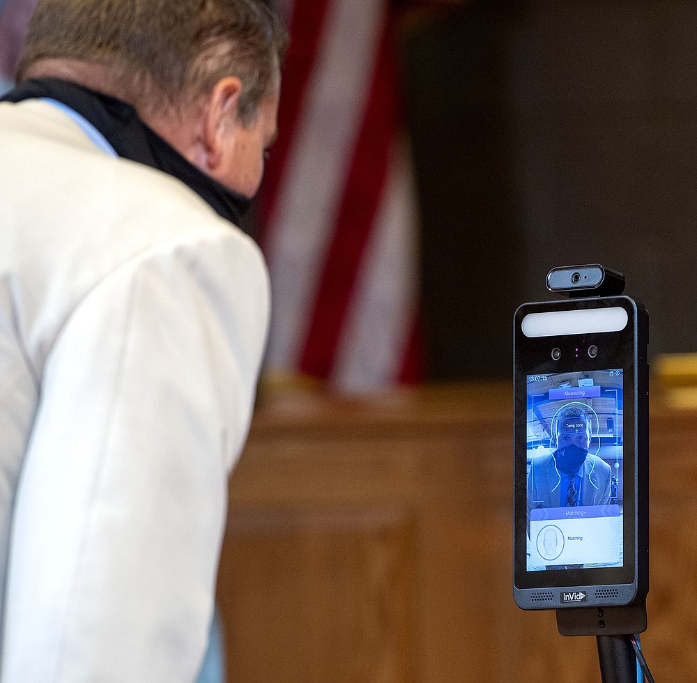 Bristol, Va., Public Schools Superintendent Dr. Keith Perrigan demonstrates Thursday, July 16, 2020, in Bristol, Va., the temperature scanner that will be used at Virginia Middle and High Schools for the upcoming school year. (David Crigger/Bristol Herald Courier via AP)