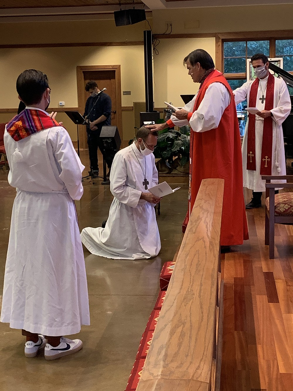 Dr. Nate Smith, kneeling, is consecrated as an Anglican priest by Bishop Phillip Jones as the Rev. Seth Richardson (left) and the Rev. Dustin Freeman (right) pray over him. (Special to the Democrat-Gazette)