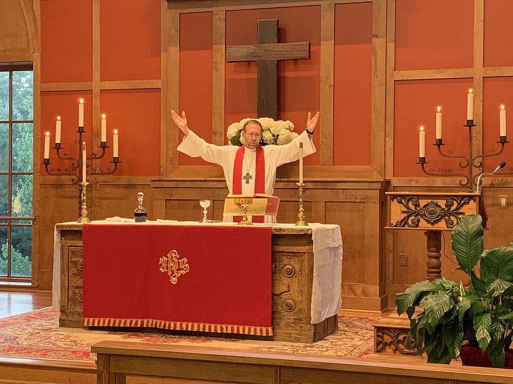 Dr. Nate Smith invites those gathered at St. Andrew's to sing the Doxology at Smith's ordination service July 15. (Special  to  the Democrat-Gazette)