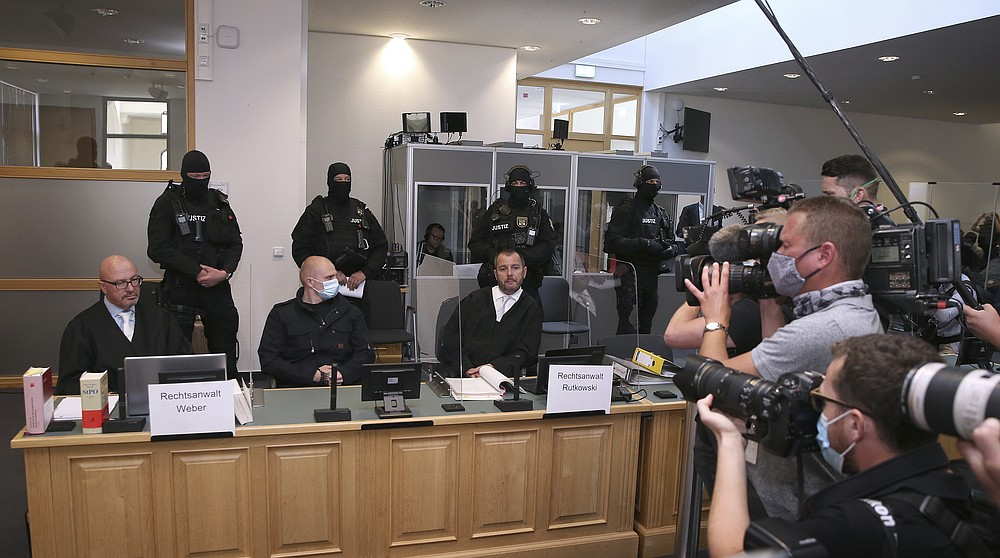 Accused Stephan Balliet, center, sits next to his  lawyers Hans-Dieter Weber, left, and Thomas Rutkowski in the regional court at the beginning of the trial in Magdeburg, Germany, Tuesday, July 21, 2020. Balliet is charged with 13 crimes including murder and attempted murder, for a Yom Kippur attack on a synagogue on Oct. 9 in the eastern German city of Halle,  that is considered one of the worst anti-Semitic assaults in the country's post-war history. (Ronny Hartmann/Pool via AP)