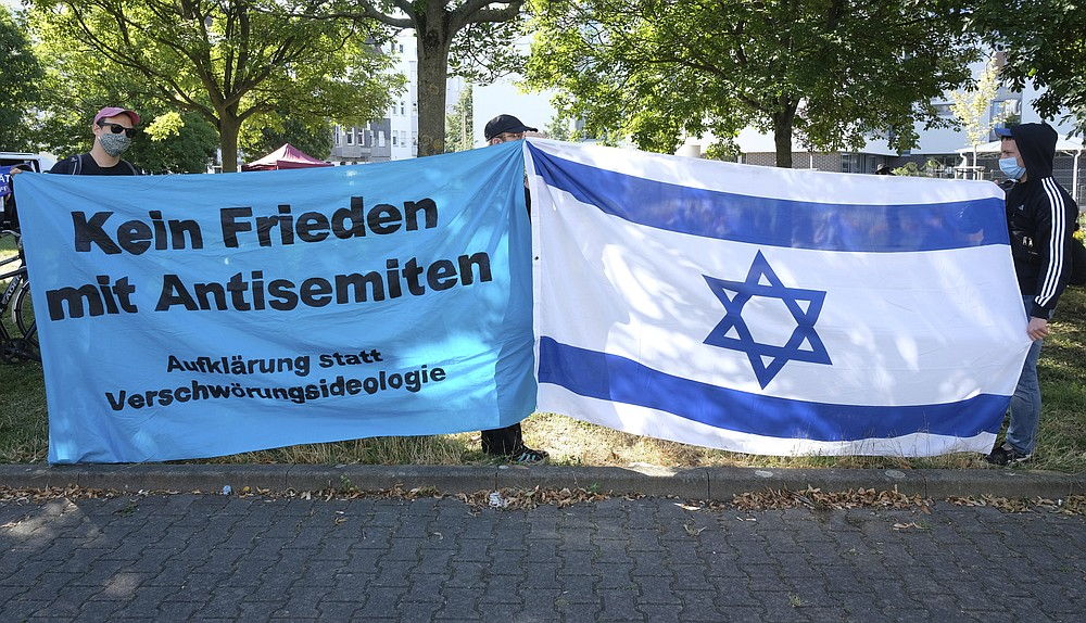 Participants of a rally stand with banners reading 'No peace with antisemites' in front of the regional court in Magdeburg, Germany, Tuesday, July 21, 2020. This is where the trial against the assassin of Halle begins. The Federal Prosecutor's Office accuses the man of 13 criminal offences, including murder and attempted murder. The assassin had tried to cause a bloodbath in the synagogue in Halle on October 9, 2019, the highest Jewish holiday Yom Kippur. (Sebastian Willnow/dpa via AP)