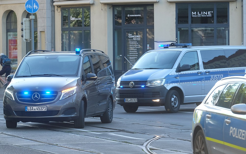 A convoy of police and justice vehicles drives with flashing blue light and siren to the Magdeburg, Germany, Tuesday, July 21, 2020. Here the trial against the assassin of Halle begins. The Federal Prosecutor's Office accuses the man of 13 crimes, including murder and attempted murder. The assassin had tried to cause a bloodbath in the synagogue in Halle on October 9, 2019, the highest Jewish holiday Yom Kippur. (Sebastian Willnow/dpa via AP)