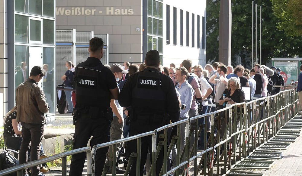Trial observers and journalists stand before the  Regional Court in Magdeburg, Germany, Tuesday, July 21, 2020. This is where the trial against the assassin of Halle begins. The Federal Prosecutor's Office accuses the man of 13 criminal offences, including murder and attempted murder. The assassin had tried to cause a bloodbath in the synagogue in Halle on October 9, 2019, the highest Jewish holiday Yom Kippur. (Sebastian Willnow/dpa via AP)