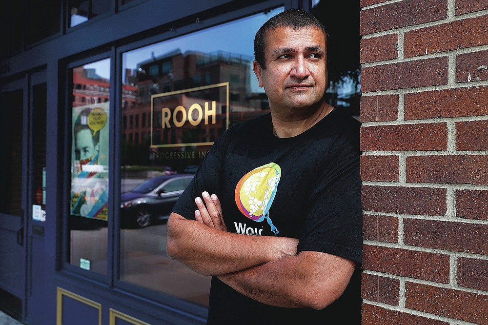 """Manish Mallick, owner of the Indian restaurant ROOH, poses for a portrait outside the West Loop restaurant in Chicago on Tuesday, July 14, 2020. When Mallick opened last year, he was focused on building his business and getting rave reviews about the eatery's """"progressive Indian cuisine"""" from the city's top critics. Now some of his biggest fans are on the city's South Side, where he regularly delivers hundreds of meals to those hardest-hit by the pandemic. (AP Photo/Charles Rex Arbogast)"""
