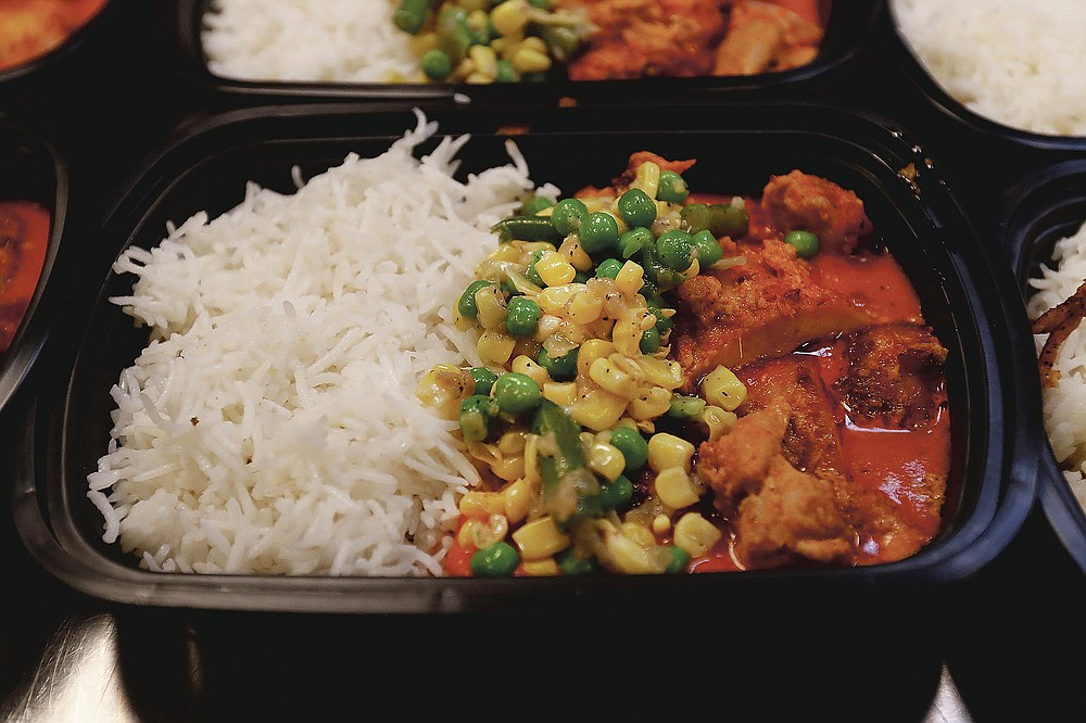Tandoori Chicken with rice, beans, peas, and sweet corn in a makhani sauce is one of two dishes prepared at the Indian restaurant ROOH, that will be delivered to I Grow Chicago in the Englewood neighborhood of Chicago on Monday, July 13, 2020. ROOH is one of hundreds of eateries around the nation working with the non-profit organization World Central Kitchen to produce meals for the hungry. (AP Photo/Charles Rex Arbogast)
