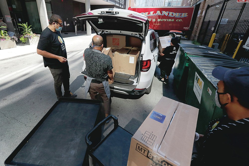 ROOH owner Manish Mallick, left, and Executive Chef Sujan Sarkar supervise the loading of 450 meals in Mallick's car for I Grow Chicago, in the Englewood neighborhood of Chicago on Monday, July 13, 2020. ROOH is one of hundreds of eateries around the nation working with the non-profit organization World Central Kitchen to provide meals to the hungry. (AP Photo/Charles Rex Arbogast)