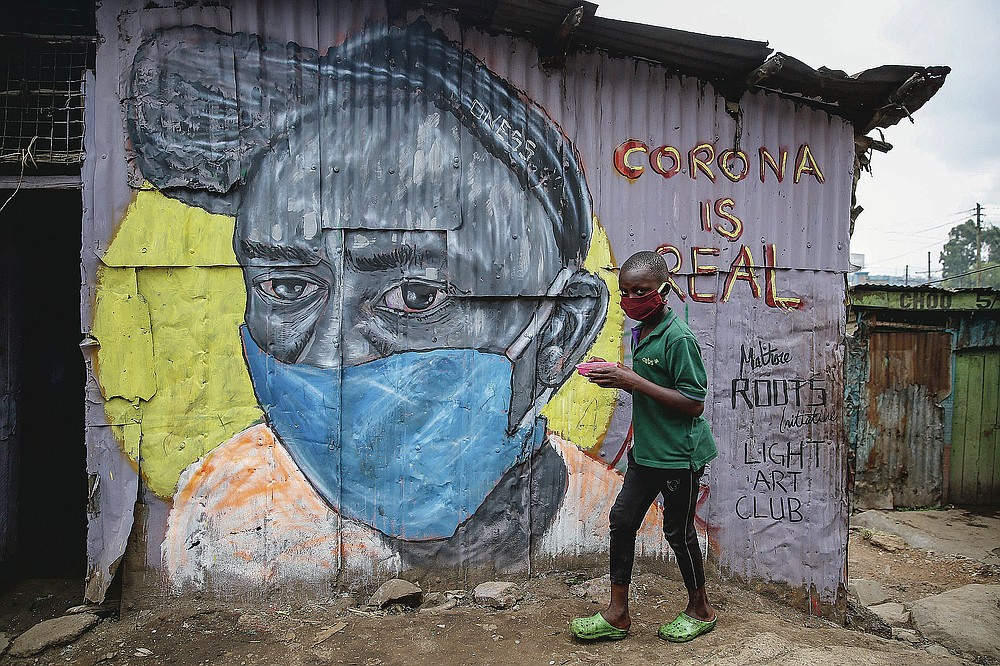 """FILE - In this April 18, 2020, file photo, a boy wearing a face mask carries a small bowl of """"githeri"""", or mixed beans and maize, for him to eat as he walks past a mural warning people about the risk of the coronavirus, painted by graffiti artists from the Mathare Roots youth group, in the Mathare slum, of Nairobi, Kenya. The options for African students eager to keep studying while schools remain closed because of the coronavirus pandemic seems varied, but the reality for many is that they will fall behind and possibly drop out of school forever, worsening inequality on an already unequal continent. (AP Photo/Brian Inganga, File)"""