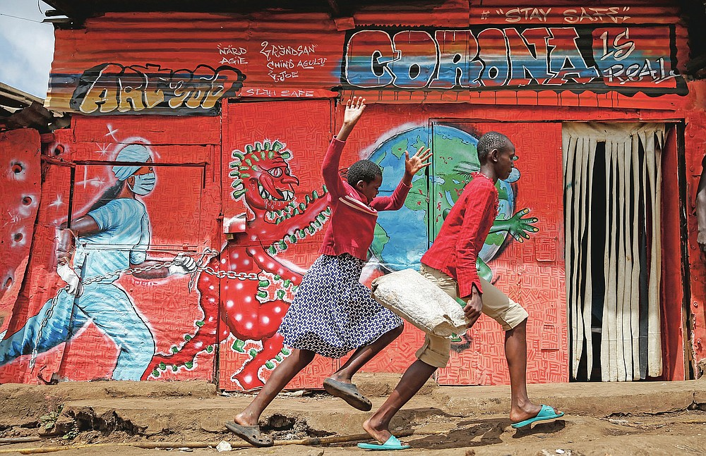 FILE - In this June 3, 2020, file photo, children run down a street past an informational mural warning people about the dangers of the new coronavirus, in the Kibera slum, or informal settlement, of Nairobi, Kenya. The options for African students eager to keep studying while schools remain closed because of the coronavirus pandemic seems varied, but the reality for many is that they will fall behind and possibly drop out of school forever, worsening inequality on an already unequal continent. (AP Photo/Brian Inganga, File)