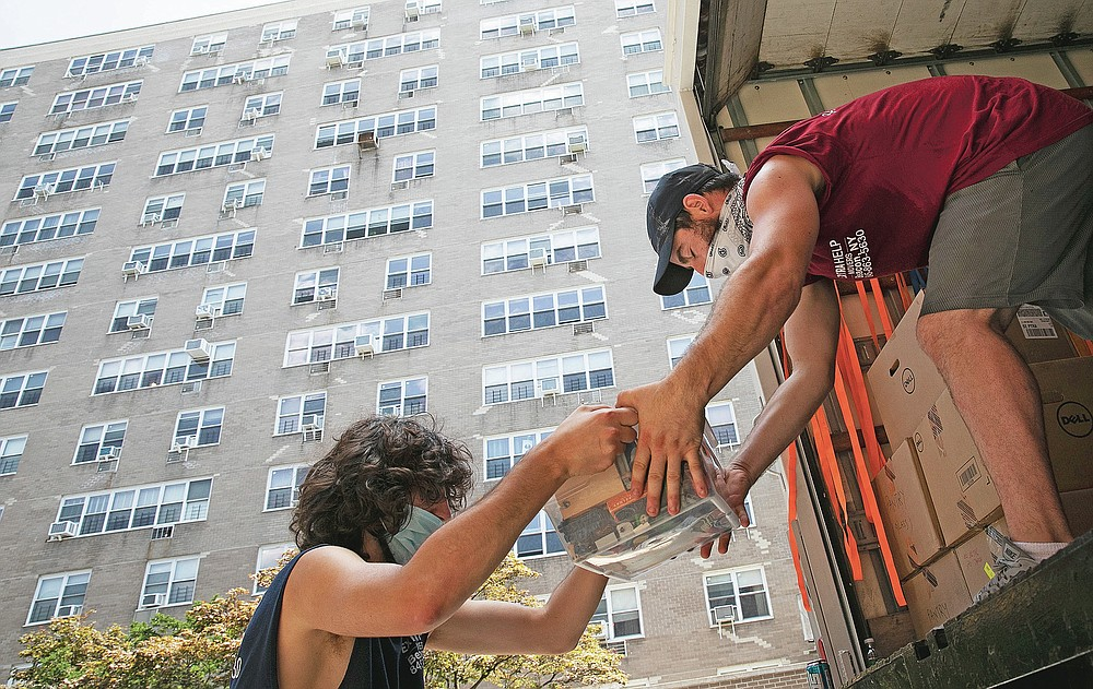 Jakob Howell, left, and Matt Brown load boxes belonging to Joyce and Anil Lilly into a moving truck, Tuesday, July 21, 2020, in The Bronx borough of New York. The Lilly's are leaving their 14th floor apartment and are moving to a town an hour's drive north, amid the coronavirus pandemic. (AP Photo/Mark Lennihan)