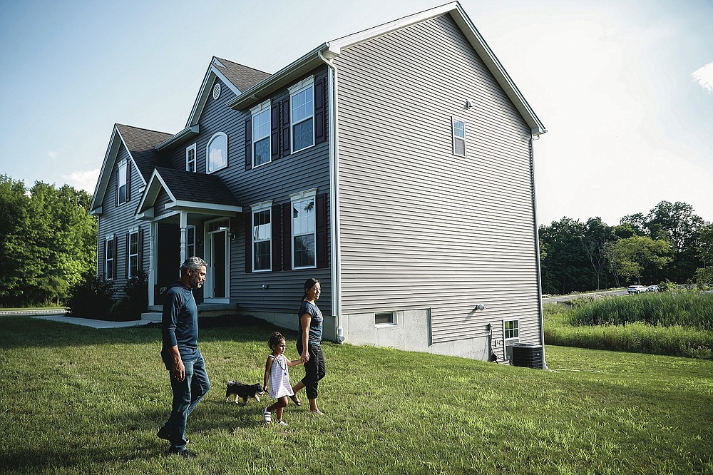 Joyce Lilly, right, holds her granddaughter Paige's hand alongside her husband, Anil, and dog Max at their new home, Tuesday, July 21, 2020, in Washingtonville, N.Y. New Yorkers anxious after weathering the worst of the coronavirus pandemic are fueling a boom in home sales and rentals around the picturesque towns and wooded hills to the north. Real estate brokers and agents describe a red-hot market recently, with many house hunters able to work from home. (AP Photo/John Minchillo)