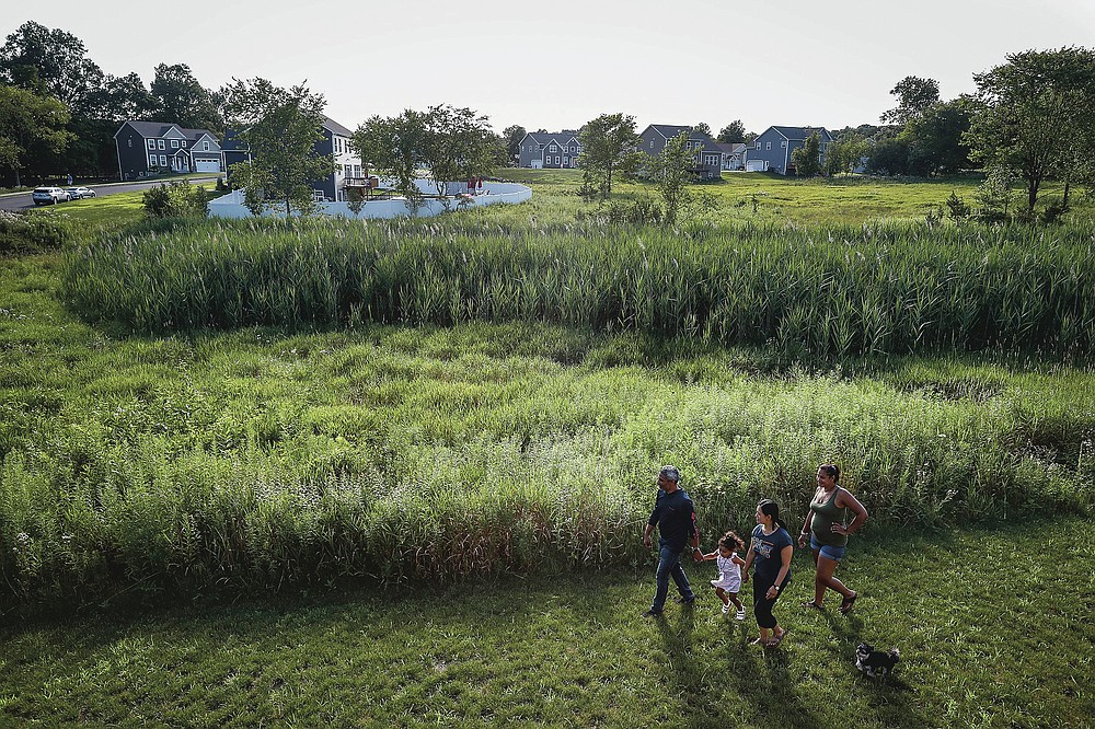 From left, Anil Lilly, granddaughter Paige, wife Joyce, and daughter Britney tour their new home, along with their dog Max, Tuesday, July 21, 2020, in Washingtonville, N.Y. New Yorkers anxious after weathering the worst of the coronavirus pandemic are fueling a boom in home sales and rentals around the picturesque towns and wooded hills to the north. Real estate brokers and agents describe a red-hot market recently, with many house hunters able to work from home. (AP Photo/John Minchillo)