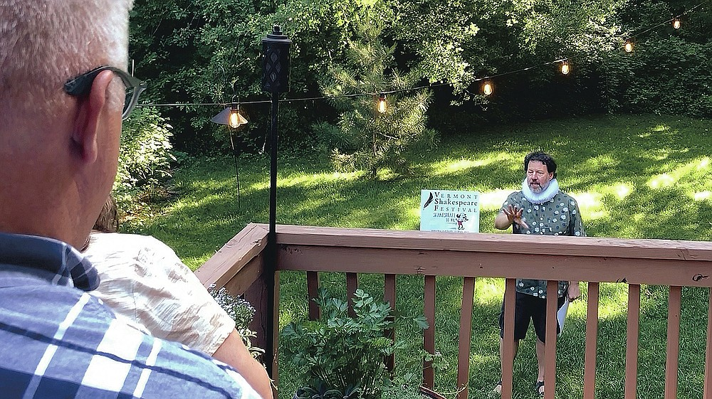 """Homeowners Jean Andre, foreground, and Jen DeBedout watch John Nagle, of the Vermont Shakespeare Festival, perform """"Shakespeare,"""" in their backyard, Thursday, June 25, 2020, in Burlington, Vt. The idea for the program known as """"Shakespeare to You,"""" or """"Bard to Your Yard,"""" was conceived as a way to keep live theater alive at a time when many social activities are being postponed or canceled amid the coronavirus pandemic. Actors with the festival have done more than 30 performances, live, online and by telephone. (AP Photo/Wilson Ring)"""