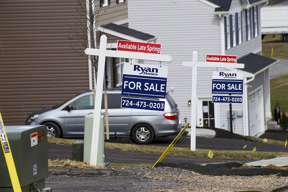 Model homes and for sale signs line the streets as construction continues at a housing plan in Zelienople, Pa., Wednesday, March 18, 2020. U.S. new home sales fell 4.4% in February with bigger declines expected in coming months as the coronavirus puts a major crimp on home sales. (AP Photo/Keith Srakocic)