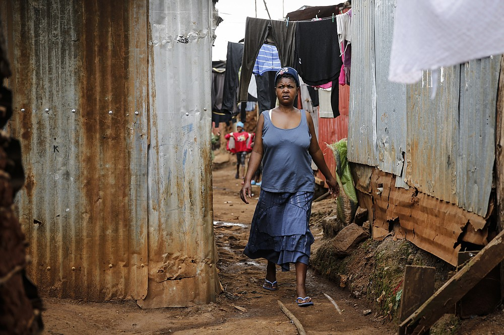 Traditional birth attendant Emily Owino walks down an alley near her home, where she assists women in delivering babies, in the Kibera slum of Nairobi, Kenya Friday, July 3, 2020. Kenya already had one of the worst maternal mortality rates in the world, and though data are not yet available on the effects of the curfew aimed at curbing the spread of the coronavirus, experts believe the number of women and babies who die in childbirth has increased significantly since it was imposed mid-March. (AP Photo/Brian Inganga)