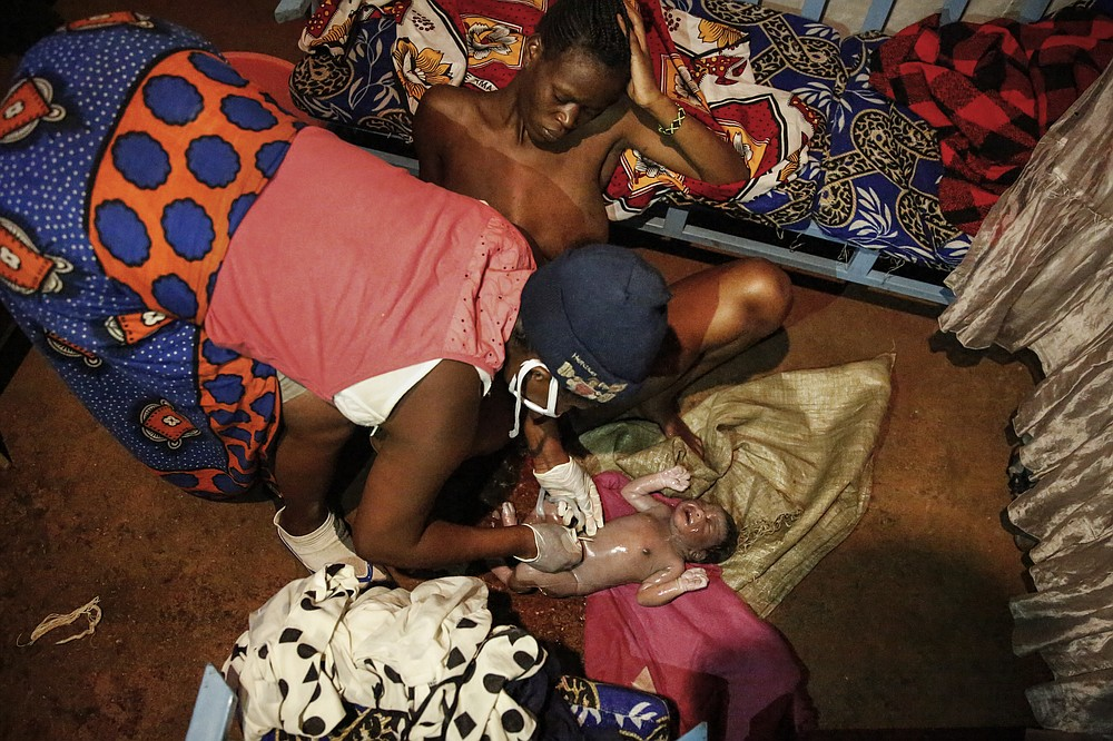 Traditional birth attendant Emily Owino, left, cuts with a razor blade the umbilical cord of newborn daughter Shaniz Joy Juma after she was delivered by her mother Veronica Atieno, center, in Emily's one-room house during a dusk-to-dawn curfew, in the Kibera slum of Nairobi, Kenya in the early hours of Friday, May 29, 2020. Kenya already had one of the worst maternal mortality rates in the world, and though data are not yet available on the effects of the curfew aimed at curbing the spread of the coronavirus, experts believe the number of women and babies who die in childbirth has increased significantly since it was imposed mid-March. (AP Photo/Brian Inganga)