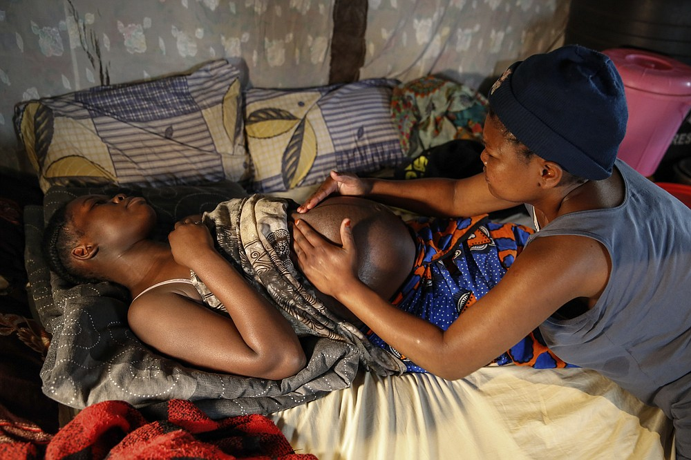 Traditional birth attendant Emily Owino, right, massages a pregnant woman, before assisting in delivering her baby, in the Kibera slum of Nairobi, Kenya Friday, July 3, 2020. Kenya already had one of the worst maternal mortality rates in the world, and though data are not yet available on the effects of the curfew aimed at curbing the spread of the coronavirus, experts believe the number of women and babies who die in childbirth has increased significantly since it was imposed mid-March. (AP Photo/Brian Inganga)