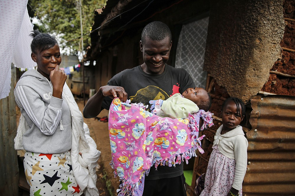 Mother Veronica Atieno, left, looks on as her husband Gabriel Owour Juma holds their daughter Shaniz Joy Juma, delivered a month earlier by a traditional birth attendant during a dusk-to-dawn curfew, accompanied by elder daughter Valine Shalom Juma, right, in the Kibera slum of Nairobi, Kenya Friday, July 3, 2020. Kenya already had one of the worst maternal mortality rates in the world, and though data are not yet available on the effects of the curfew aimed at curbing the spread of the coronavirus, experts believe the number of women and babies who die in childbirth has increased significantly since it was imposed mid-March. (AP Photo/Brian Inganga)