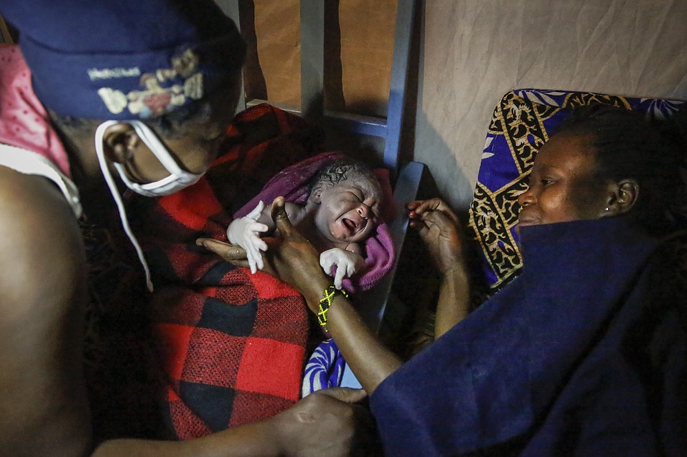 Traditional birth attendant Emily Owino, left, hands over newborn daughter Shaniz Joy Juma, center, to her mother Veronica Atieno, right, after she was born in Emily's one-room house during a dusk-to-dawn curfew, in the Kibera slum of Nairobi, Kenya in the early hours of Friday, May 29, 2020. Kenya already had one of the worst maternal mortality rates in the world, and though data are not yet available on the effects of the curfew aimed at curbing the spread of the coronavirus, experts believe the number of women and babies who die in childbirth has increased significantly since it was imposed mid-March. (AP Photo/Brian Inganga)