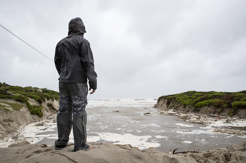 A man stands at the top of a dune at the end of Access Road 5 and watches as Hurricane Hanna approaches land in Corpus Christi, Texas, Saturday, July 25, 2020  Hanna has been upgraded to a hurricane and is moving toward Texas, which has been dealing with a surge of coronavirus cases in recent weeks. The National Hurricane Center said Saturday morning that Hanna's maximum sustained winds had increased and that it was expected to make landfall Saturday afternoon or early evening. (Courtney Sacco/Corpus Christi Caller-Times via AP)