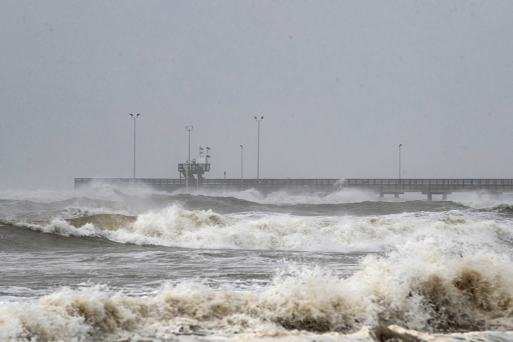 Tides rise at Bob Hall Pier as Hurricane Hanna approaches land in Corpus Christi, Texas on Saturday, July 25, 2020. Hanna has been upgraded to a hurricane and is moving toward Texas, which has been dealing with a surge of coronavirus cases in recent weeks. The National Hurricane Center said Saturday morning that Hanna's maximum sustained winds had increased and that it was expected to make landfall Saturday afternoon or early evening. (Courtney Sacco/Corpus Christi Caller-Times via AP)