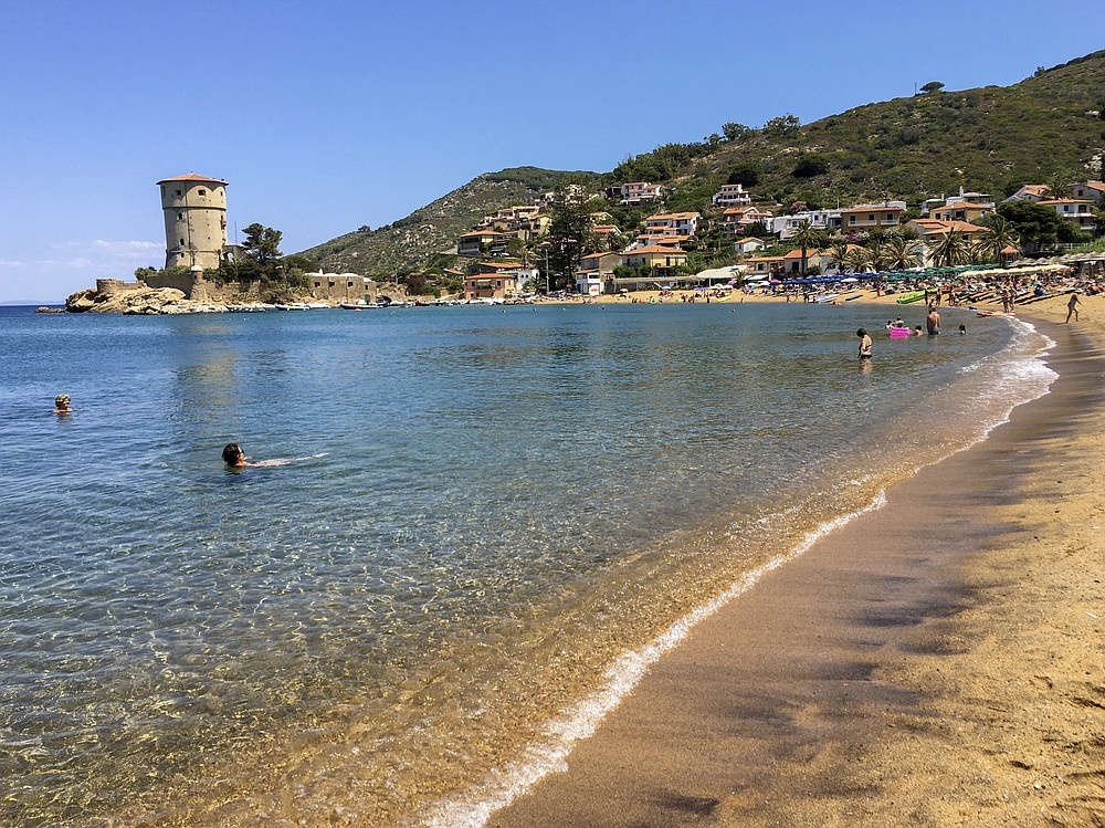 People enjoy the sun and the fresh water on a beach at the Giglio island, in front of Tuscany, Italy, Wednesday, June 24, 2020. In spite of various people with coronavirus stopped by the island at times, no one of the islanders developed COVID-19 infection. (AP Photo/Paolo Santalucia)