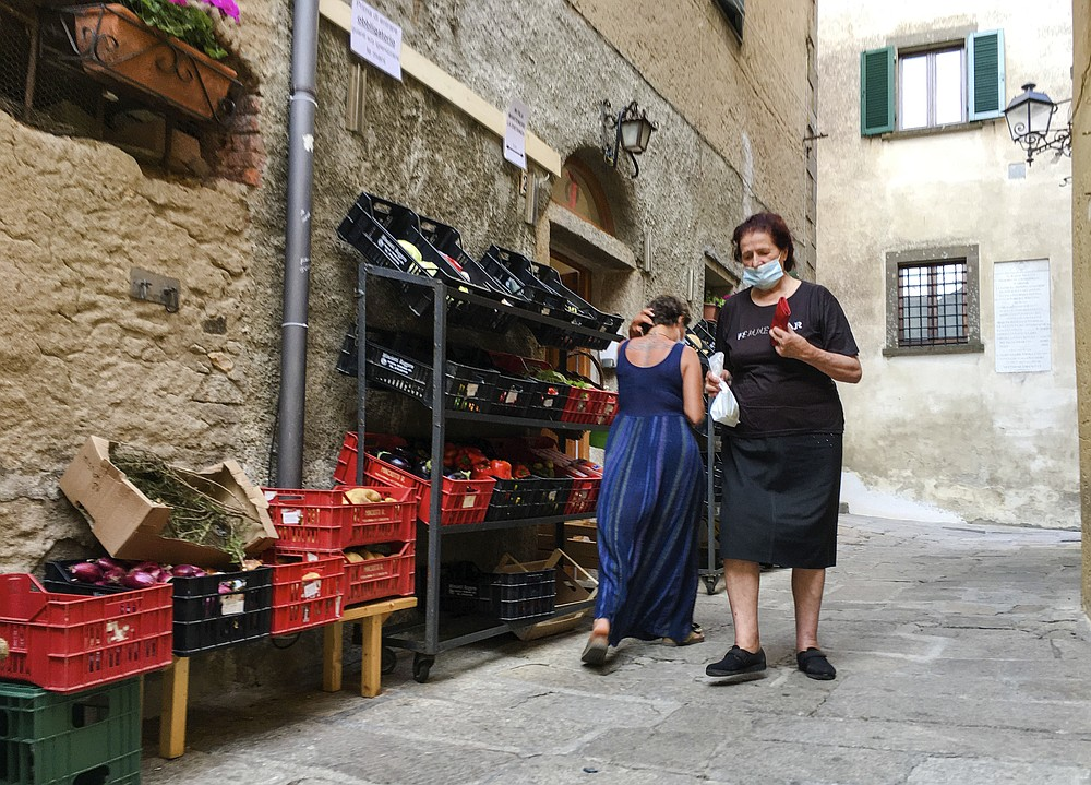Residents of Giglio island shop in the steep alleys near the port, Tuesday, June 23, 2020. In spite of various people with coronavirus stopped by the island at times, no one of the islanders developed COVID-19 infection. For Paola Muti, a professor of Epidemiology, being trapped by lockdown in her late mother's house for months on Giglio Island, the situation also made for an opportunity to possibly contribute to scientific understanding of why some people in close contact with people ill with COVID-19 don't get infected. (AP Photo/Paolo Santalucia)
