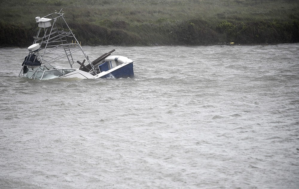 A boat sinks in the Packery Channel during Hurricane Hanna, Saturday, July 25, 2020, in North Padre Island, Texas. The Category 1 storm continued to strengthen before reaching Padre Island at 5 p.m. Saturday. (Annie Rice/Corpus Christi Caller-Times via AP)