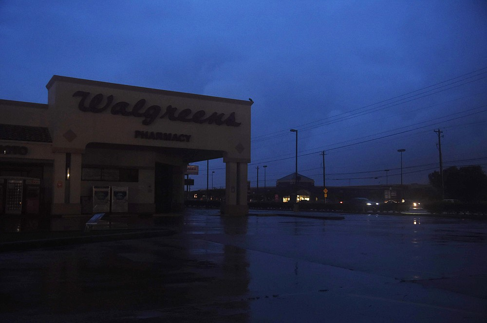 A darkened Walgreens is seen off of Saratoga and Staples during Hurricane Hanna, Saturday, July 25, 2020, in Corpus Christi, Texas. As of mid-Saturday, AEP Texas reports 16,564 power outages in Nueces County. (Annie Rice/Corpus Christi Caller-Times via AP)