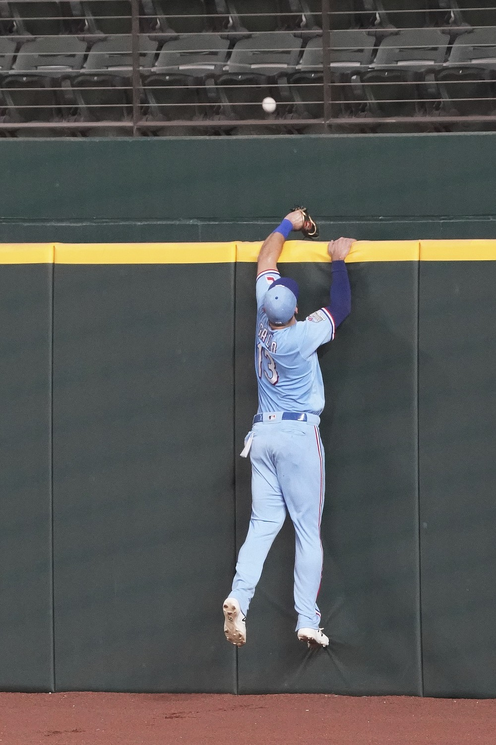Texas Rangers right fielder Joey Gallo leaps at the wall but cannot reach a home run by Colorado Rockies' Trevor Story in the fourth inning of a baseball game Sunday, July 26, 2020, in Arlington, Texas. (AP Photo/Louis DeLuca)