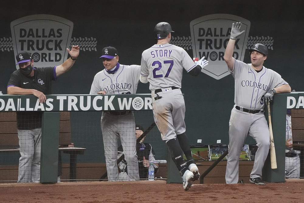 Colorado Rockies' Trevor Story (27) is congratulated at the dugout after his home run in the fourth inning of a baseball game against the Texas Rangers, Sunday, July 26, 2020, in Arlington, Texas. (AP Photo/Louis DeLuca)