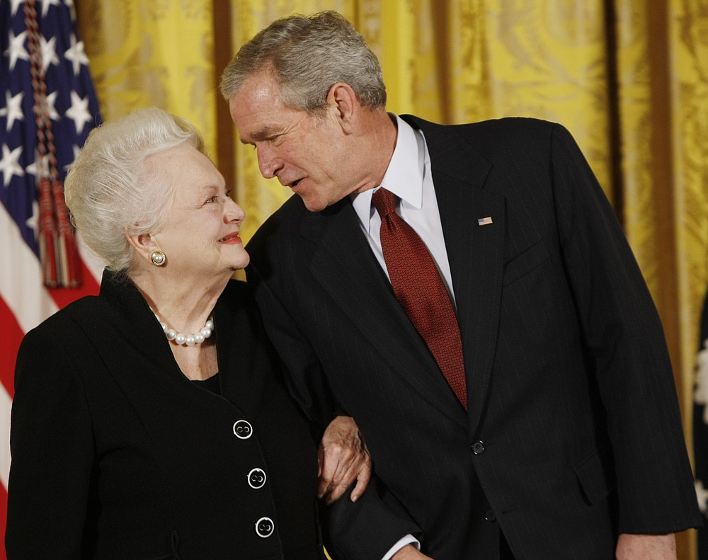 FILE - In this file photo dated Monday, Nov. 17, 2008, US President George W. Bush greets actress Olivia de Havilland as he presented her with the 2008 National Medals of Arts, in the East Room of the White House in Washington, USA. Olivia de Havilland, Oscar-winning actress has died, aged 104 in Paris,  publicist says Sunday July 26, 2020. (AP Photo/Gerald Herbert, FILE)