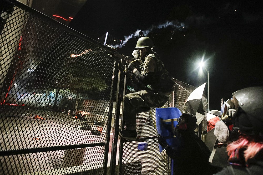 A demonstrator tries to climb over a fence during a Black Lives Matter protest at the Mark O. Hatfield United States Courthouse Sunday, July 26, 2020, in Portland, Ore. (AP Photo/Marcio Jose Sanchez)