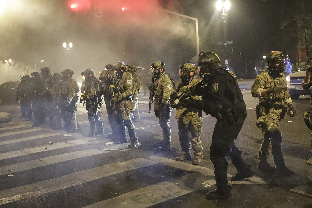 Federal officers line up to deploy tear gas at demonstrators during a Black Lives Matter protest at the Mark O. Hatfield United States Courthouse Sunday, July 26, 2020, in Portland, Ore. (AP Photo/Marcio Jose Sanchez)