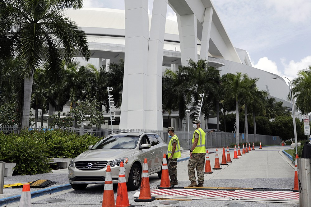 Members of the Florida National Guard monitor vehicles at a COVID-19 testing site outside of Marlins Park, Monday, July 27, 2020, in Miami. The Marlins home opener against the Baltimore Orioles on Monday night has been postponed as the Marlins deal with a coronavirus outbreak that stranded them in Philadelphia. (AP Photo/Lynne Sladky)