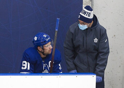 Toronto Maple Leafs centre John Tavares (91) speaks with a trainer after taking a hit during first period intrasquad NHL hockey training camp action in Toronto on Thursday, July 23, 2020. (Nathan Denette/The Canadian Press via AP)