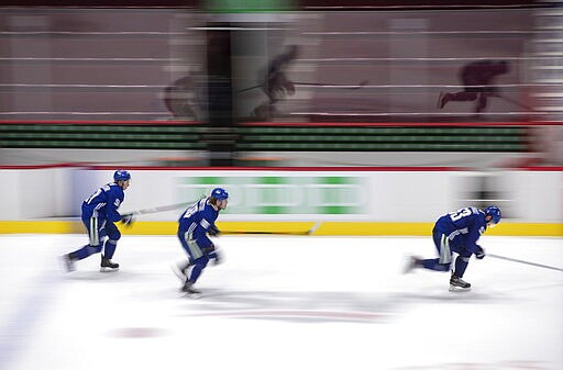 Vancouver Canucks' Troy Stecher, from left to right, Adam Gaudette and Bo Horvat skate during the NHL hockey team's training camp in Vancouver, on Wednesday, July 22, 2020. (Darryl Dyck/The Canadian Press via AP)