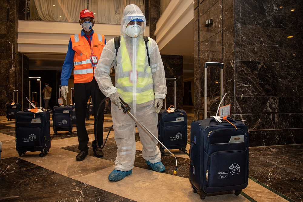 In this July 26, 2020, photo, the luggage of pilgrims is sanitized in a hotel lobby in Mecca ahead of the annual hajj pilgrimage. The Islamic pilgrimage has been dramatically downsized this year with only a few thousand residents of Saudi Arabia permitted to take part due to concerns over the coronavirus. (Saudi Ministry of Media)