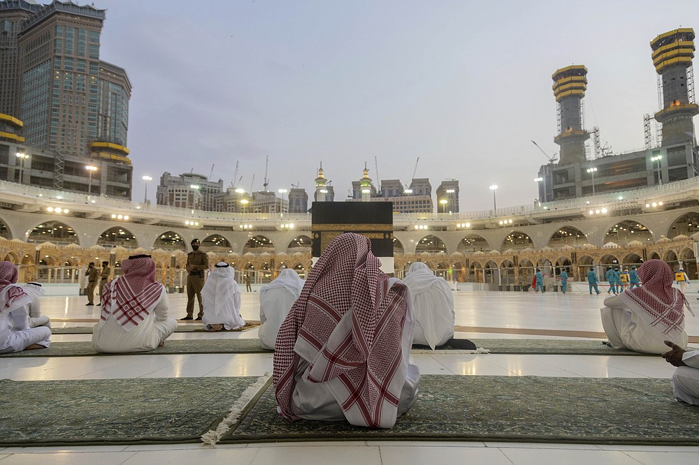 Pilgrims pray around the Kaaba, the square structure in the Great Mosque, toward which believers turn when praying, in Mecca, Saudi Arabia, late Sunday, July 26, 2020. Anywhere from 1,000 to 10,000 pilgrims will be allowed to perform the annual hajj pilgrimage this year due to the virus pandemic. (Saudi Ministry of Media via AP)