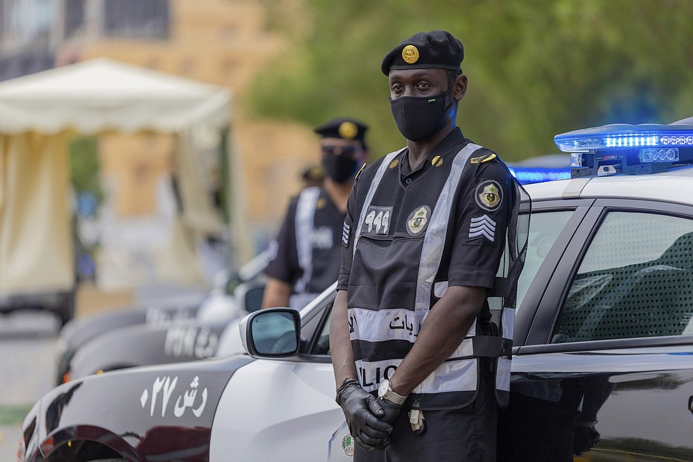 Policemen wearing gloves and face masks to help prevent the spread of the coronavirus, provide security for pilgrims, in Mecca, Saudi Arabia, Sunday, July 26, 2020. Only about 1,000 pilgrims will be allowed to perform the annual hajj pilgrimage that begins later this month due to the virus pandemic. (Saudi Ministry of Media via AP)