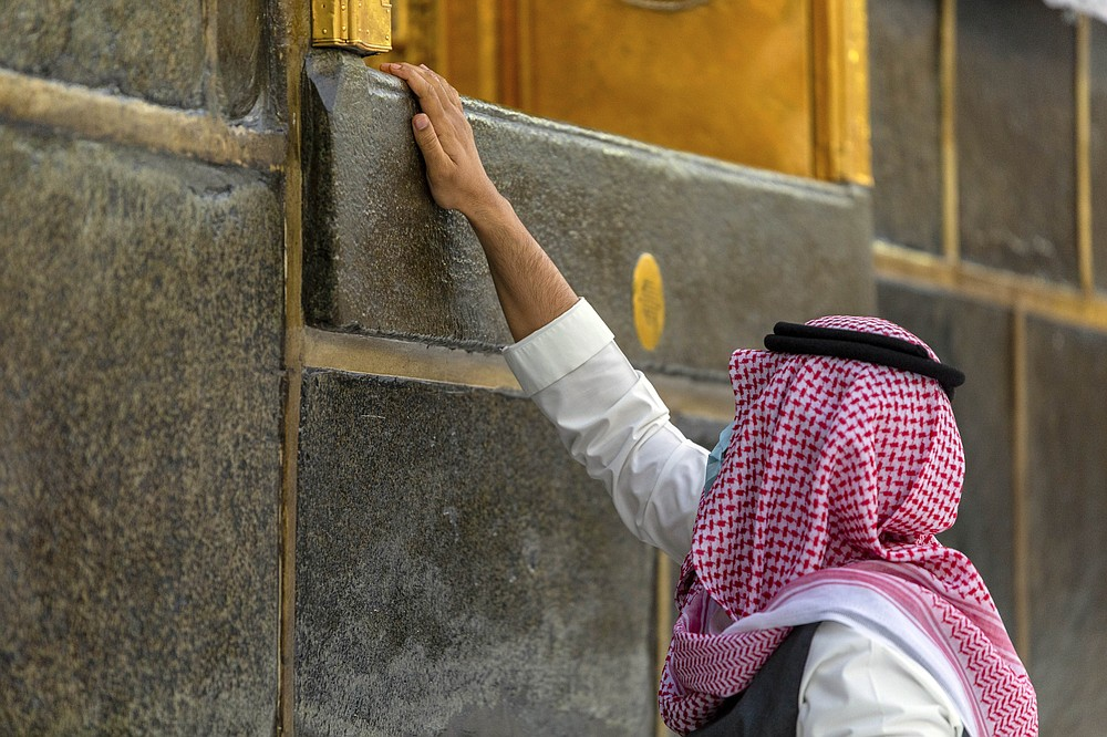 A pilgrim touches the Kaaba, the square structure in the Great Mosque, toward which believers turn when praying, in Mecca, Saudi Arabia, Monday, July 27, 2020. Anywhere from 1,000 to 10,000 pilgrims will be allowed to perform the annual hajj pilgrimage this year due to the coronavirus pandemic. (Saudi Ministry of Media via AP)